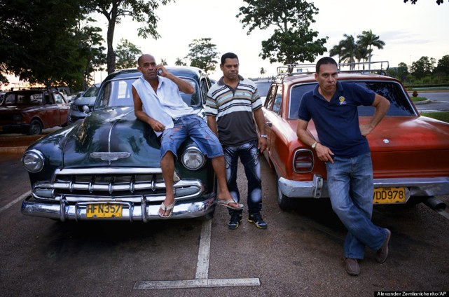 Drivers relax at their American classic cars at the Jose Marti international airport in Havana, Cuba, Tuesday, June 25, 2013. (AP Photo/Alexander Zemlianichenko)
